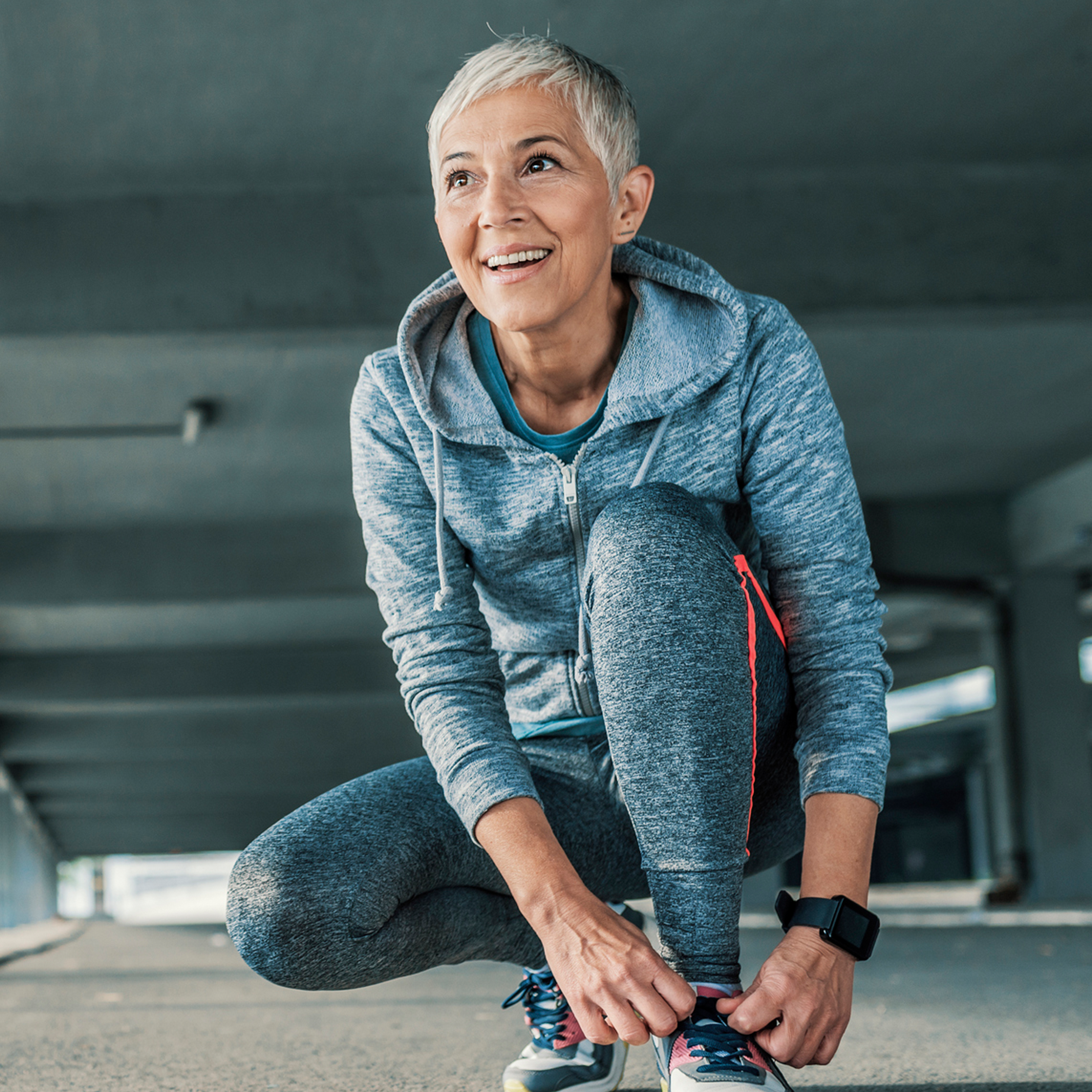 mature woman putting on running shoes